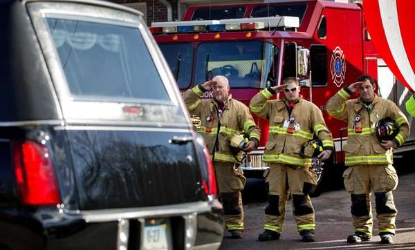 Firefighters salute as a hearse passes for the