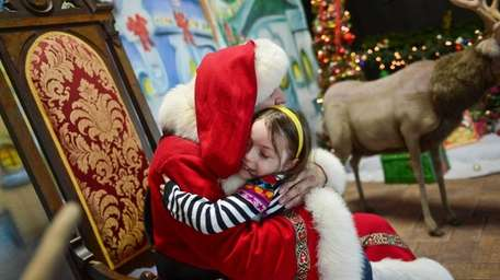 Lana Landa, 5, of Oceanside hugs Santa Claus