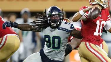 Seattle Seahawks defensive end Jadeveon Clowney (L) pressures