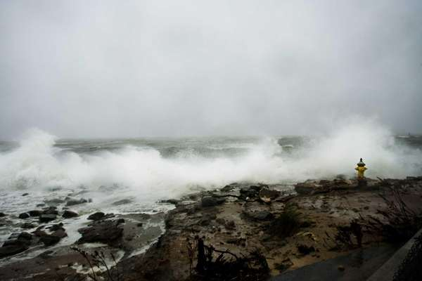 A storm surge pushes waves over rocks on