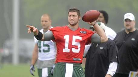 Quarterback Tim Tebow #15 directs a wide receiver