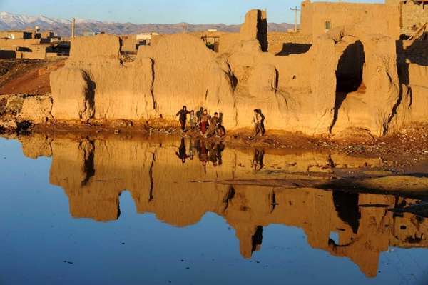 Afghan children play near a lake on