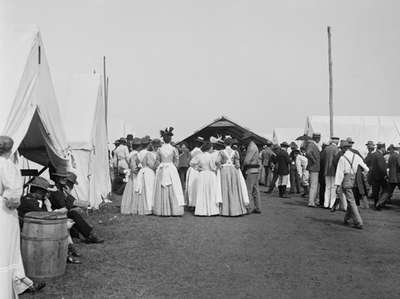 Nurses standing near hospital tents among a crown