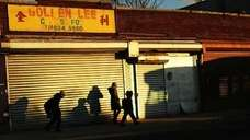 People walk by shuttered businesses in the heavily