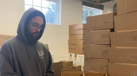 Distiller Ryan Carpenter places labels on Long Island