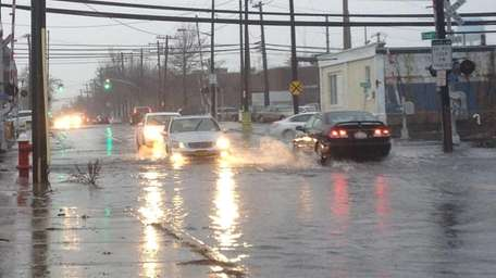 Cars go through large puddles on Willis ave