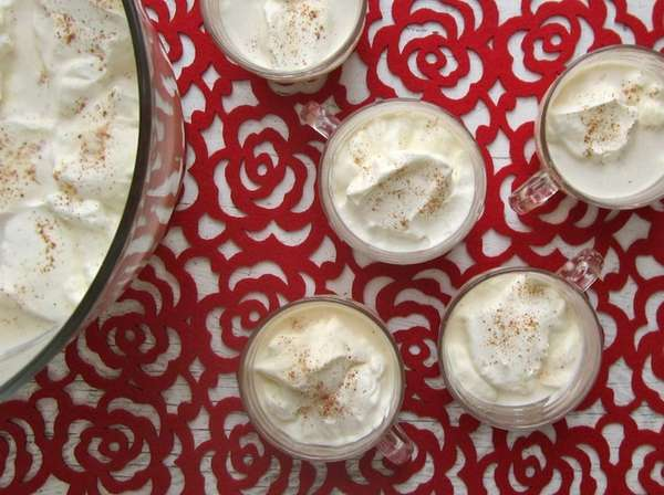 Whipped cream floated on top of eggnog lightens