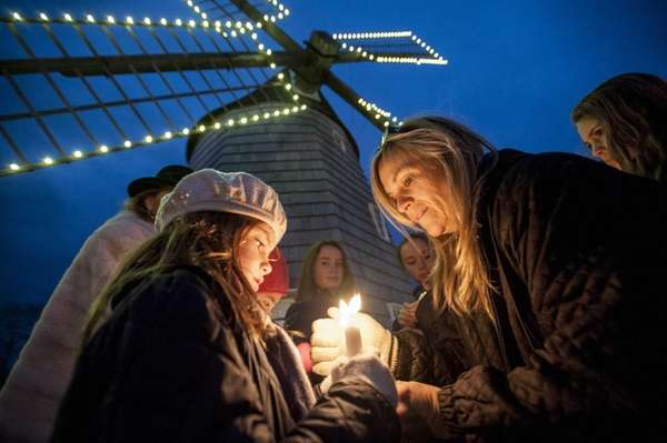 Bonnie Boisits, right, helps light the candle of