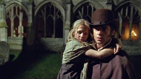 Hugh Jackman as Jean Valjean holding Isabelle Allen