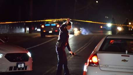 A Suffolk County police officer ropes off the