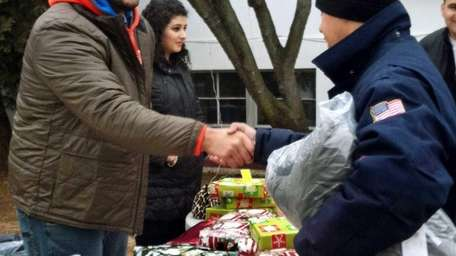 Football player Oday Aboushi, left, helps distribute presents