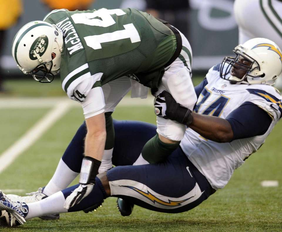 Jets quarterback Greg McElroy is brought down by