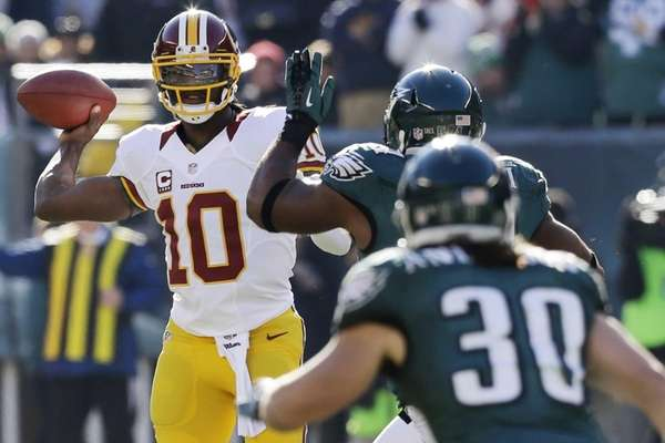 Washington Redskins quarterback Robert Griffin III, left, passes