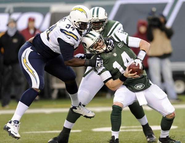 Jets quarterback Greg McElroy, right, is sacked by