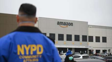 An NYPD Community Affairs officer watches as Amazon