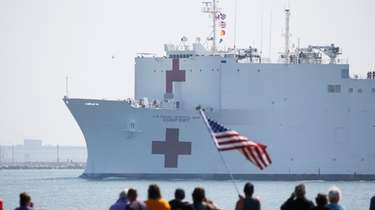 Local residents watch as the USNS Comfort departs