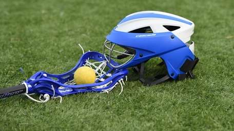 A lacrosse helmet, stick and ball on the