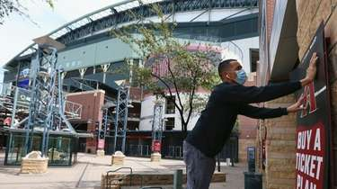 Joey Rodriguez, of Image Craft, installs an advertising
