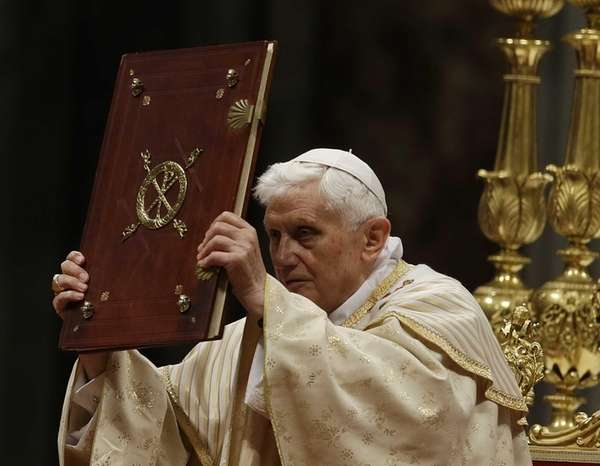 Pope Benedict XVI holds up the Book of