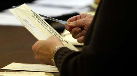 A poll worker opens an absentee ballot.