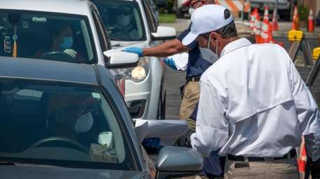 Workers in Hialeah, Fla., distribute paper applications for