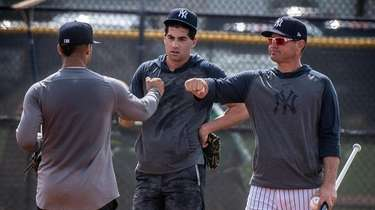 Yankees infield coach Carlos Mendoza, right, talks with