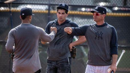 Yankees infield coach Carlos Mendoza, right, talks with