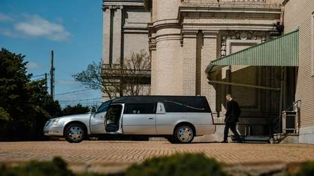 Nick Cassese puts cremated remains in a hearse