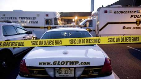 Police vehicles sit behind crime tape outside the