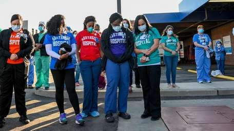 Health care workers bow their heads in prayer