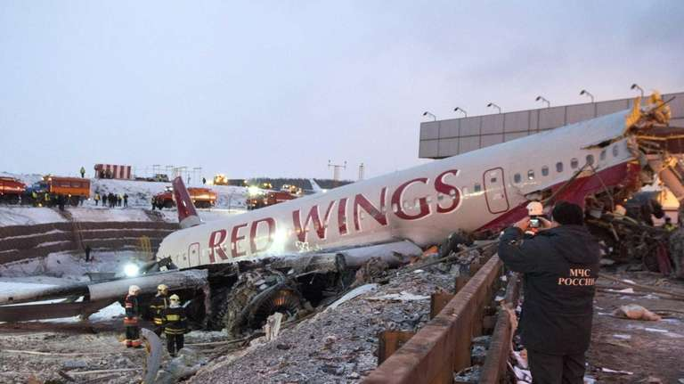 Rescuers work at the site where a plane