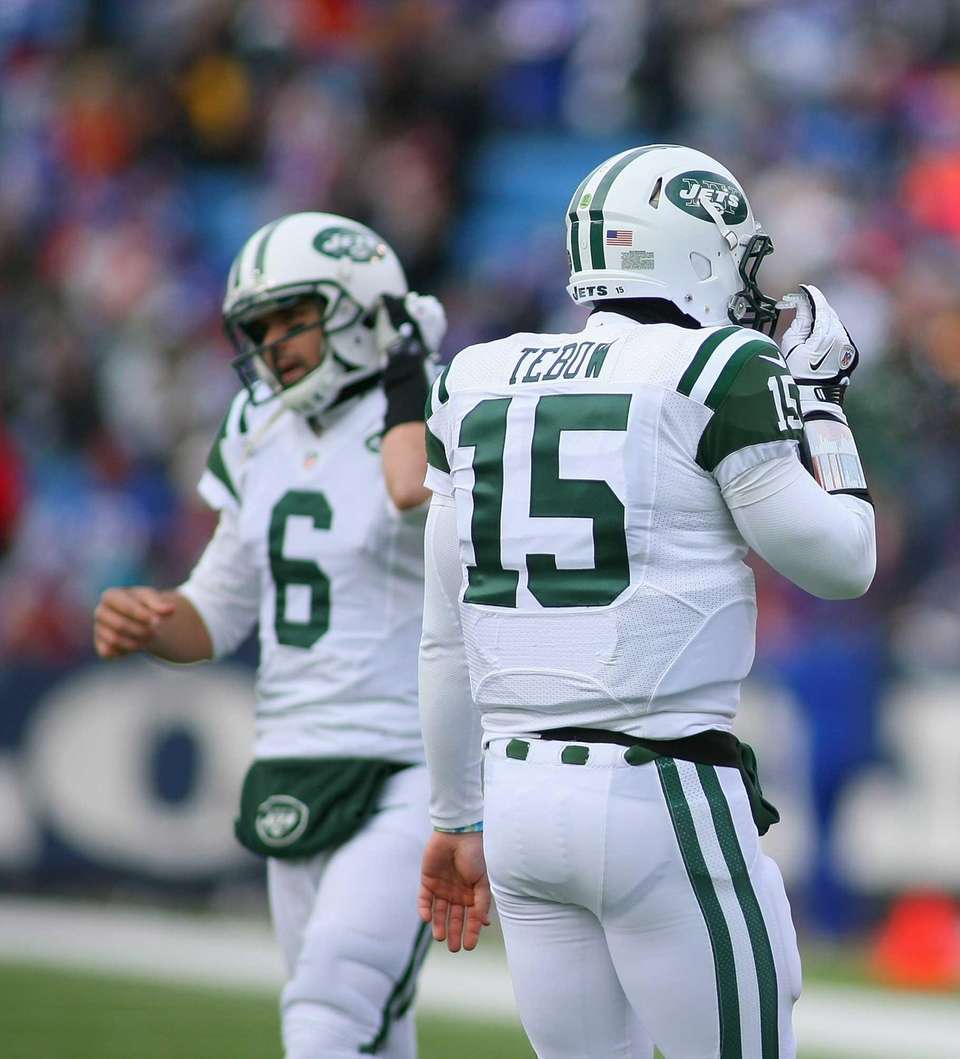 Tim Tebow, right, of the Jets walks off