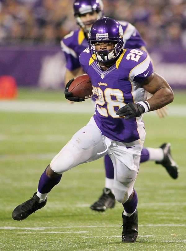 Adrian Peterson of the Minnesota Vikings runs against