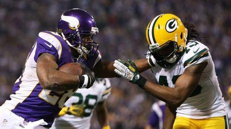 Minnesota Vikings running back Adrian Peterson, left, tries