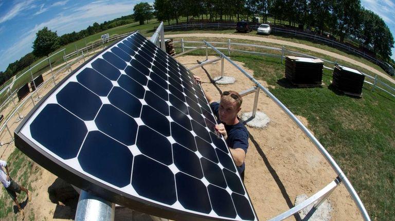 Danny Volkomer, an installer with Green Logic, installs