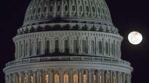 The moon rises behind the U.S. Capitol Dome