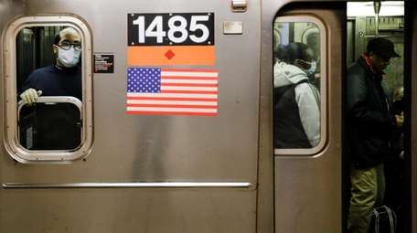 An MTA worker wears personal protective equipment at