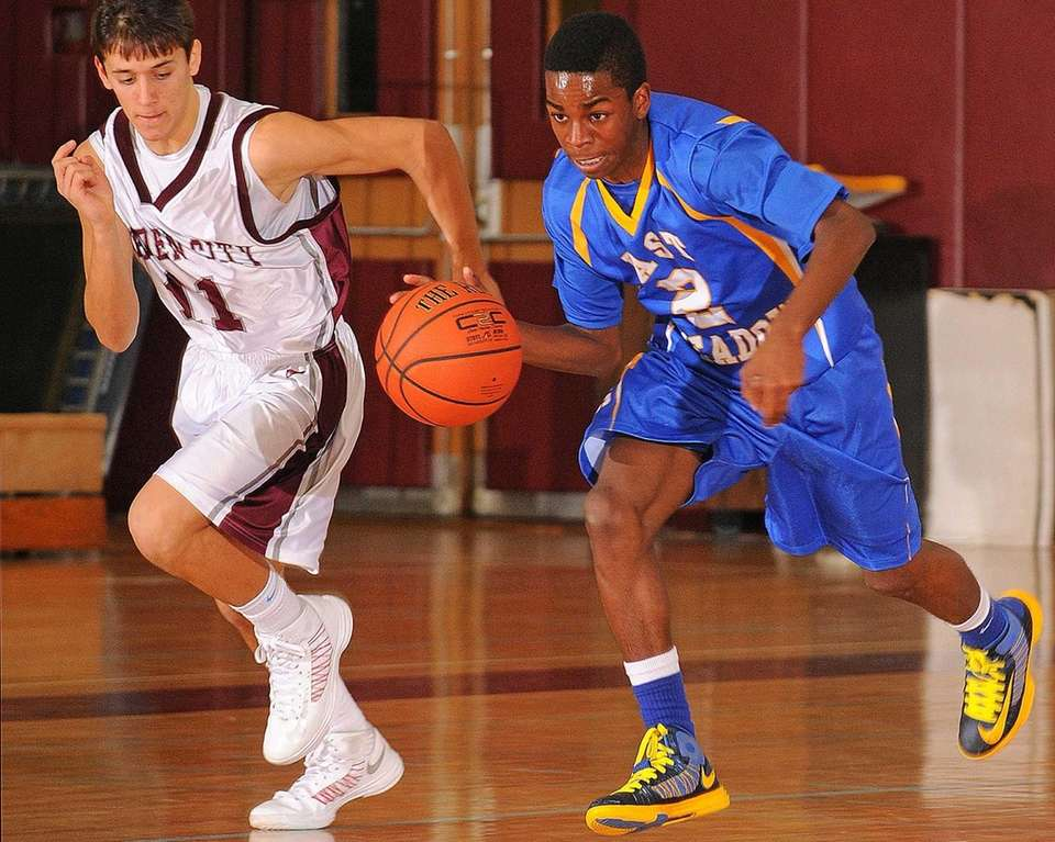 East Meadow guard Damien Sanders, right, dribbles downcourt