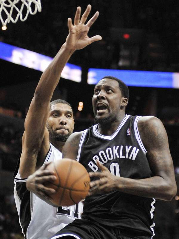 Andray Blatche, right, shoots ahead of San Antonio