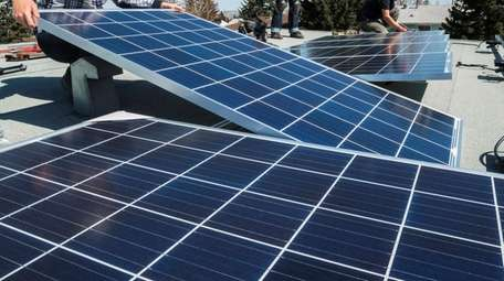 Workers installing solar panels on a residential homes