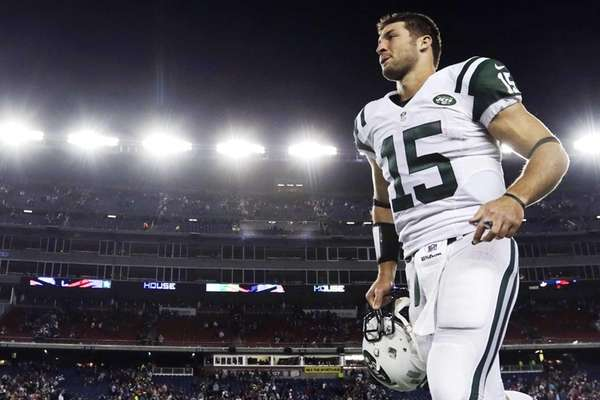 Tim Tebow leaves the field after a loss