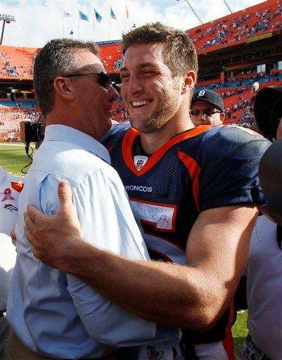 Then-Denver Broncos quarterback Tim Tebow, right, gets a