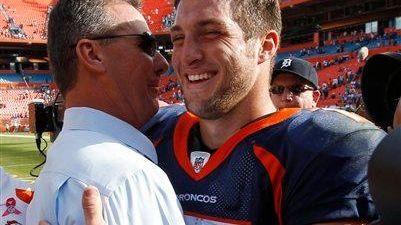 Then-Denver Broncos quarterback Tim Tebow, right, gets a