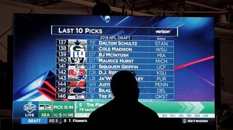 A man watches the NFL draft during a