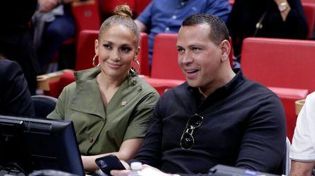 Jennifer Lopez, left, and Alex Rodriguez sit courtside