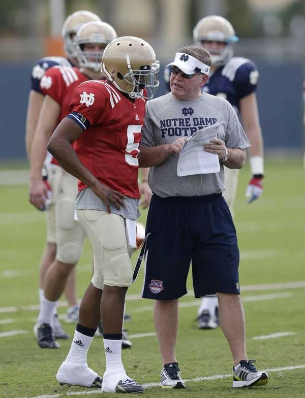 Notre Dame head coach Brian Kelly, right, talks