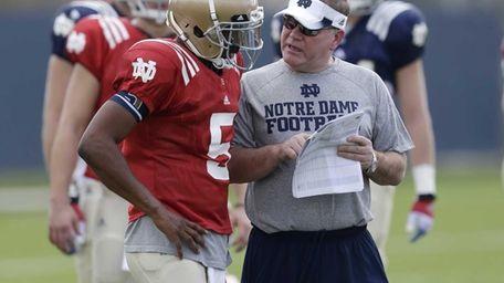 Notre Dame head coach Brian Kelly, right, talks