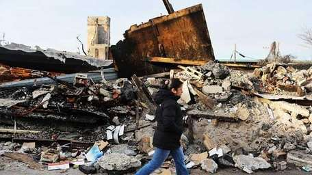 A woman walks by homes and businesses destroyed