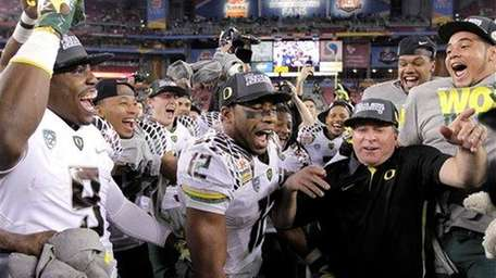 Oregon players celebrate at midfield after beating Kansas