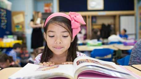 Diana Hernandez, 7, reads the story of Pinocchio,